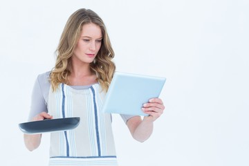 Concentrated woman holding frying pan and tablet pc