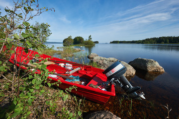 Red boat powered by the lake