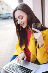 Woman with red wine tablet and laptop in street cafe