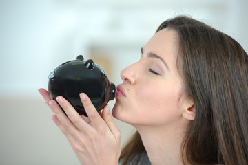 Woman putting coin into a piggy bank