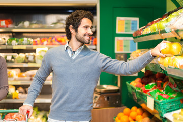 Man picking up vegetables in a grocery store