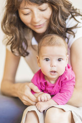Family Concept: Portrait of Young Mother Taking Care of Her Litt
