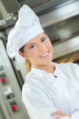 Female baker stood by bread oven