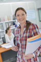 Female architect carrying folders