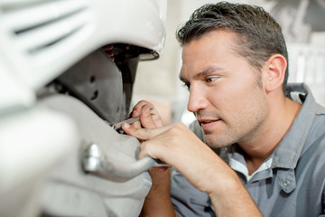 Mechanic examining a scooter