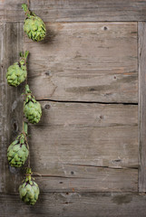 Fresh artichokes  hanging over wooden table