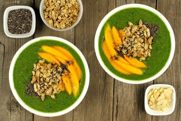 Green smoothie bowls with mango, overhead view on wood