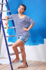 Happy beautiful young woman doing wall painting, standing on