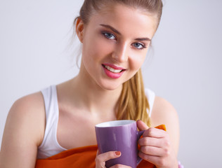 Young woman sitting with pillow and holding a cup of tea