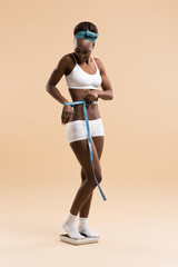 Woman standing on scale measuring waist with tape