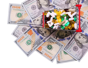 Shopping cart full with pills and capsules over dollar bills