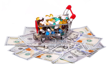 Shopping cart full with pills and capsules over money