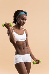 Woman pumping up muscles with dumbbells