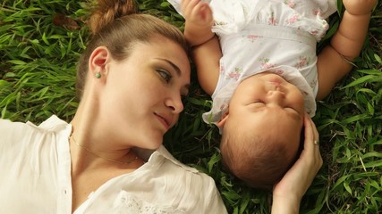 Mother Kissing Little Baby Daughter Laying Closed On Grass
