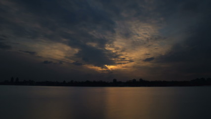 The picturesque sunset with puffy clouds above land with lake
