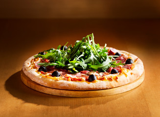 pizza with ham, salami and arugula salad