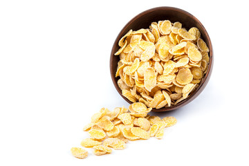 Cornflakes in a wooden bowl on white background.
