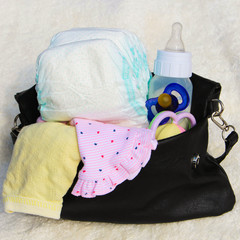 Women's handbag with items to care for the child
