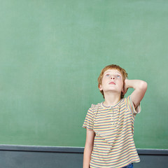 Boy standing in front of empty chalkboard