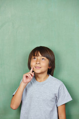 Asian boy thinking in front of chalkboard