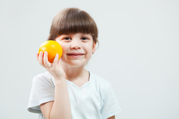 Little girl holding orange and smiling