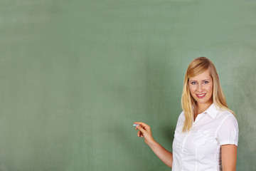Teacher with chalk in front of chalkboard