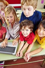 Children in elementary school with laptop