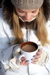Молодая девушка держит кружку кофе