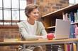 Smiling teacher using laptop at a desk