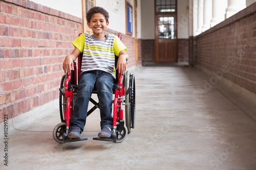 Cute disabled pupil smiling at camera in hall - 80299723