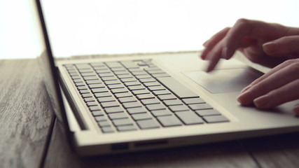 Woman Scrolls a Website Using Her Laptop