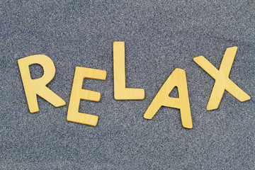 Relax written with wooden letters on blue sand