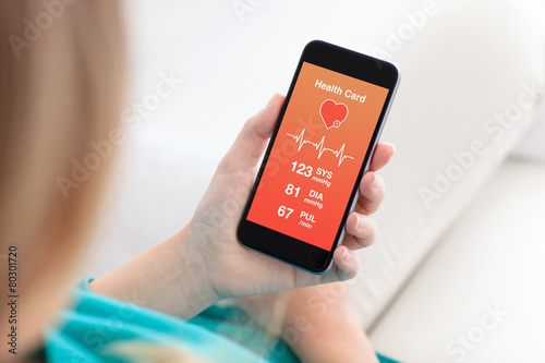 woman holding a phone with app for health card monitoring - 80301720