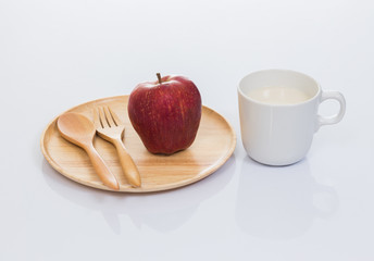 Cup of soy milk with apple and wood plate isolated on white back