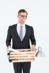 Sad geeky businessman holding box of his things