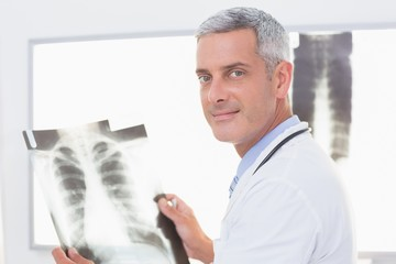 Smiling doctor looking at X-Rays
