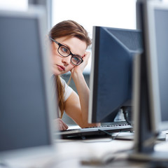 Pretty, female student looking at a desktop computer screen
