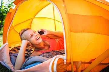 Pretty, young woman camping outdoors, lying in the tent