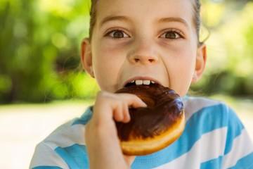 Cute little girl eating doughnut