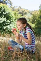 Cute little girl blowing bubbles