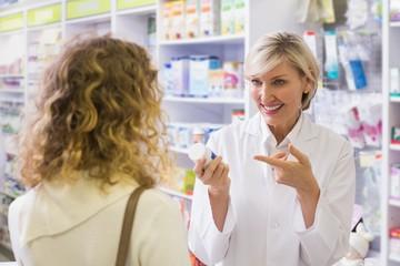 Pharmacist holding a bottle of drugs talking to customer