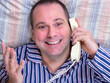 happy man with phone lying in bed