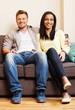 Cheerful multi-ethnic couple sitting on a sofa
