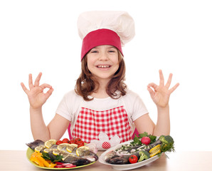 happy little girl cook with fishes and ok hand sign