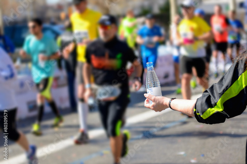 Marathon running race, runners on road, volunteer giving water - 80309579