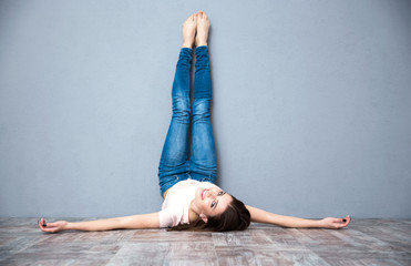 Smiling attractive woman lying on the floor with legs raised up