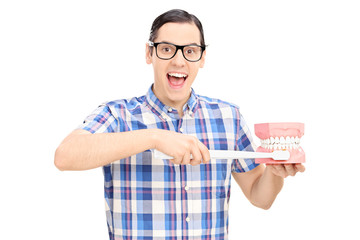 Young guy holding a denture and toothbrush