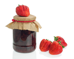 Glass jar of strawberry jam with berries isolated on white backg