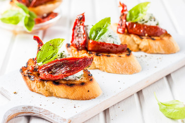 toast with cheese, basil and sun-dried tomatoes on a white board