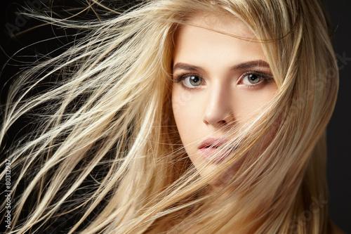 Leinwandbild Motiv Portrait of blonde girl with fluttering hair